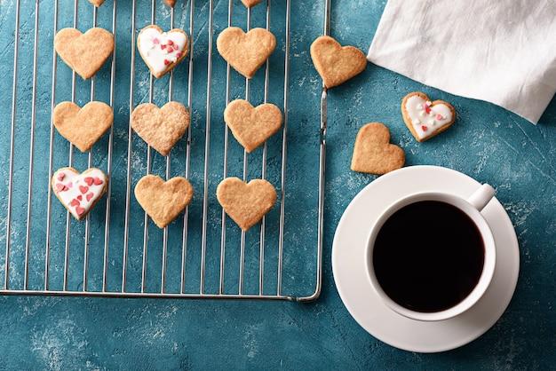 Biscoitos gelados caseiros em forma de coração na grelha de metal com uma xícara de chá vermelho