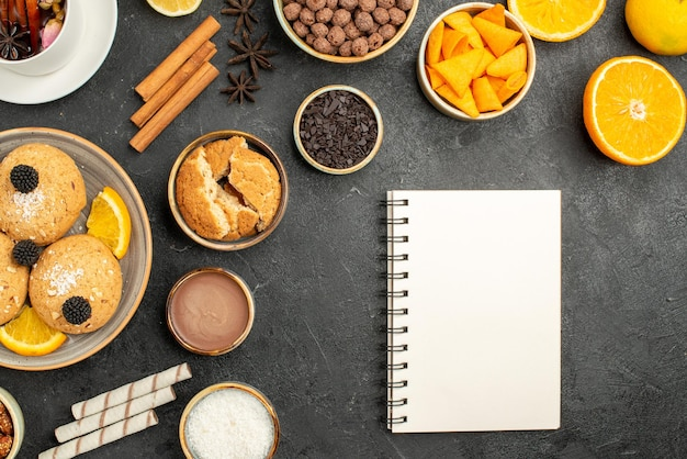 Biscoitos gostosos de vista de cima com fatias de laranja e uma xícara de chá na superfície escura torta de bolo açúcar sobremesa biscoito chá