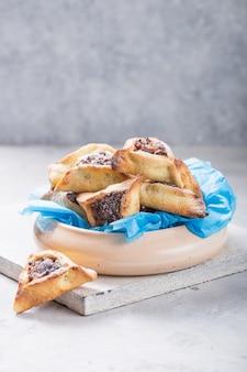 Biscoitos hamantaschen judaicos tradicionais com damascos secos, datas. conceito de celebração de purim.