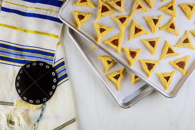 Biscoitos judaicos crus na bandeja do forno com kippa e talit.