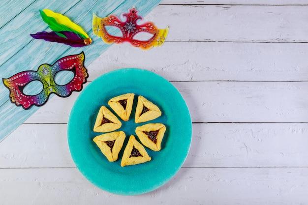 Biscoitos judaicos de purim na placa azul com máscaras.