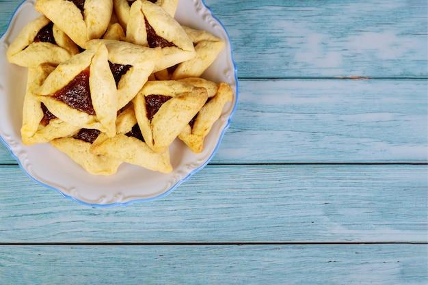 Biscoitos judaicos em chapa branca sobre fundo azul de madeira.