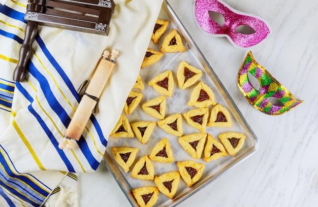 Biscoitos judaicos orelhas de hamã na assadeira para purim com máscara, talit e barulho.