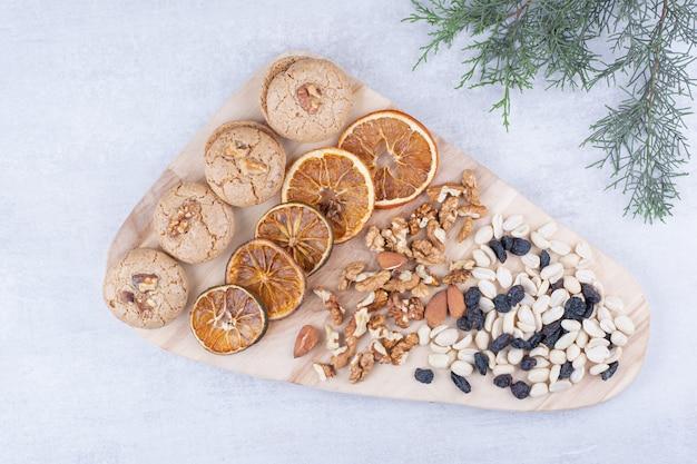 Biscoitos, laranjas e várias nozes na placa de madeira.