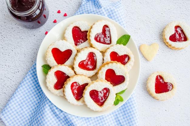 Biscoitos linzer com coração com geléia de framboesa e açúcar em pó em um prato branco com uma xícara de chá.
