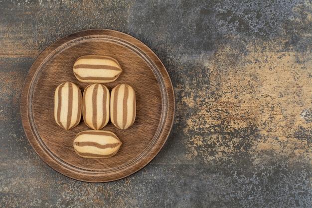 Biscoitos listrados de chocolate deliciosos na placa de madeira.