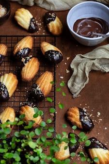 Biscoitos madeleine com cobertura de chocolate e migalhas de coco
