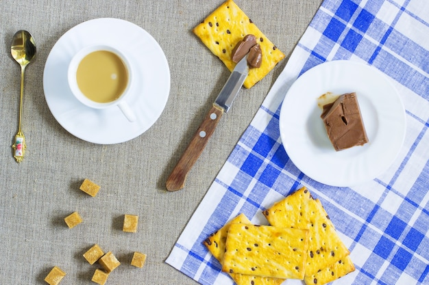 Biscoitos. manteiga de chocolate. uma xícara de café com leite