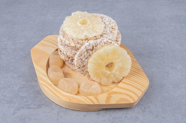 Biscoitos, marmeladas e rodelas de abacaxi secas em uma travessa de madeira sobre mármore