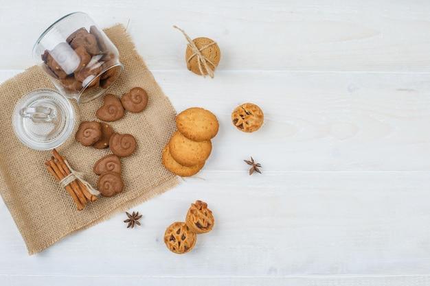 Biscoitos marrons em uma jarra, canela em um jogo americano com biscoitos brancos