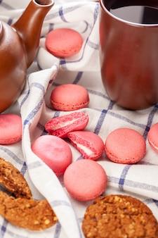 Biscoitos minúsculos rosa macaron numa toalha de mesa close-up