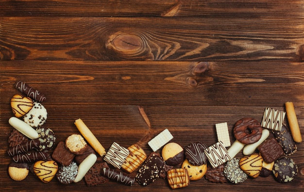 Biscoitos mistos cobertos com chocolate no fundo de madeira