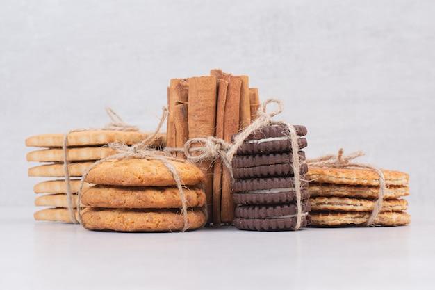 Biscoitos na corda com paus de canela na mesa branca.