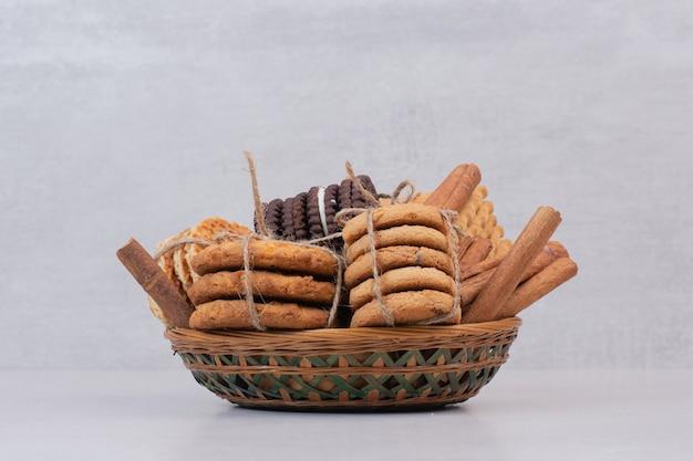 Biscoitos na corda com paus de canela na superfície branca