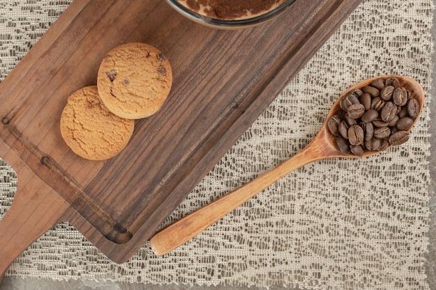 Biscoitos na tábua de madeira com grãos de café
