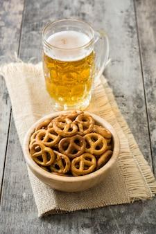 Biscoitos na tigela e cerveja na mesa de madeira