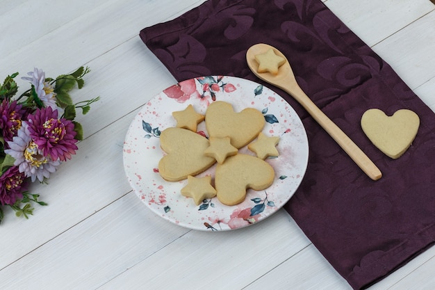 Biscoitos no prato e colher de pau com vista de alto ângulo de flores sobre fundo de madeira e têxteis