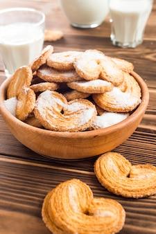 Biscoitos no prato e leite em cima da mesa