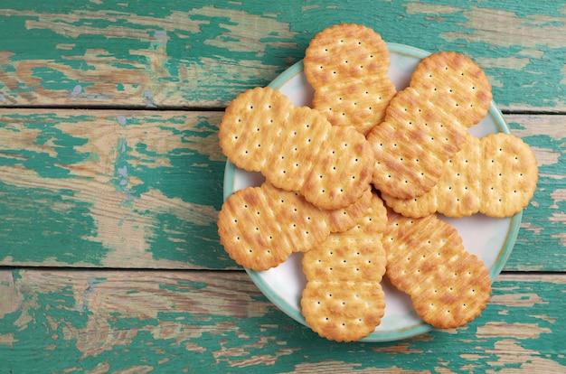 Biscoitos no prato no antigo fundo de madeira verde, vista superior