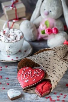 Biscoitos ou biscoitos de gengibre em uma caixa de presente com uma fita vermelha em uma mesa de madeira. dia dos namorados.