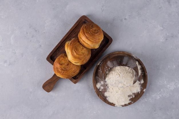 Biscoitos ou pães com farinha em uma travessa de madeira, vista superior
