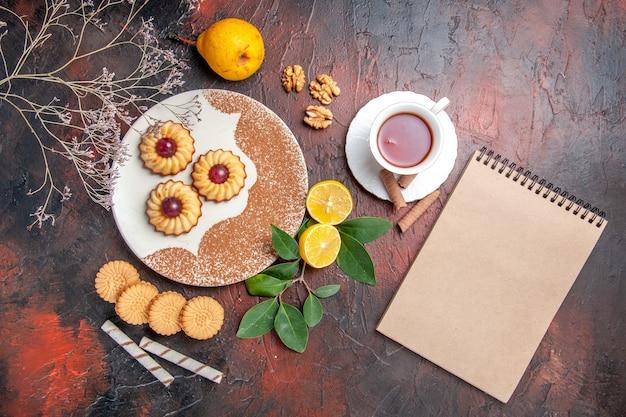 Biscoitos pequenos com uma xícara de chá na mesa escura, bolo de açúcar, biscoito doce