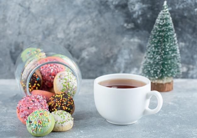 Biscoitos, pinheiro e chá na mesa de mármore.