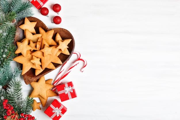 Biscoitos, presentes e galhos de pinheiro em uma mesa de madeira branca