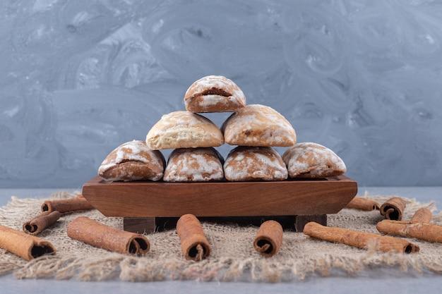 Biscoitos pryanik russos em uma pequena bandeja, rodeados de paus de canela em tecido
