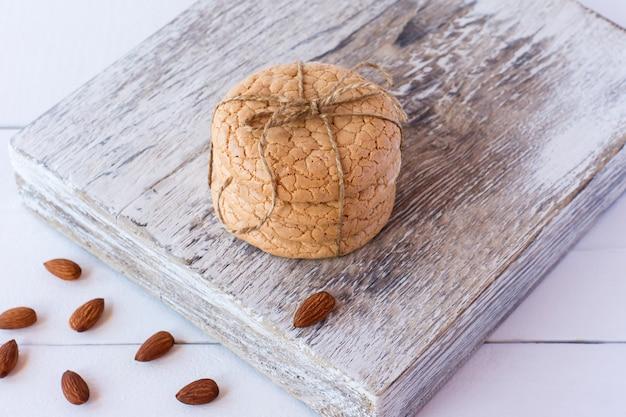 Biscoitos quaresmais úteis de farinha de amêndoa empilhados em uma tábua de madeira branca sobre fundo branco de madeira. foco seletivo.