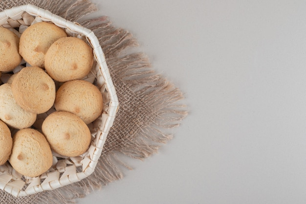 Biscoitos quebradiços em uma cesta branca em um pedaço de pano com fundo de mármore.