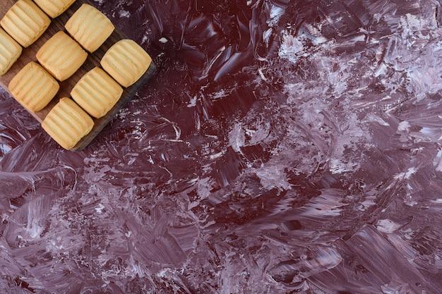 Biscoitos recém-assados em uma placa de madeira sobre uma superfície clara