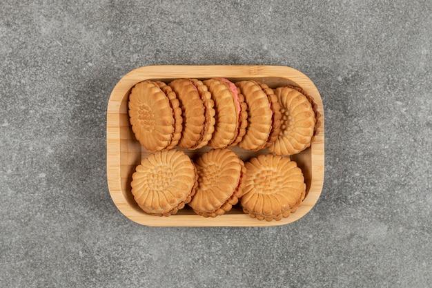 Biscoitos recheados com creme no prato de madeira