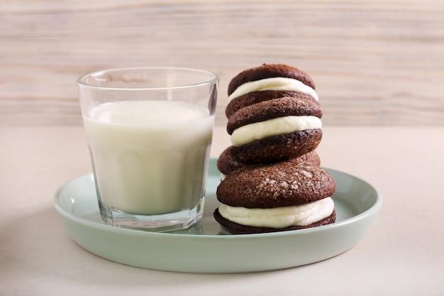 Biscoitos recheados de chocolate com recheio de natas, servidos com copo de leite