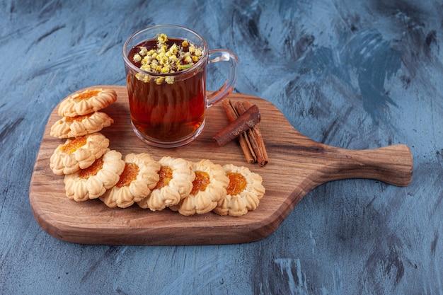 Biscoitos redondos com geleia e um copo de chá preto colocados sobre uma tábua de madeira.