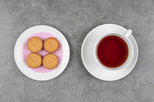 Biscoitos redondos deliciosos e xícara de chá na superfície de mármore