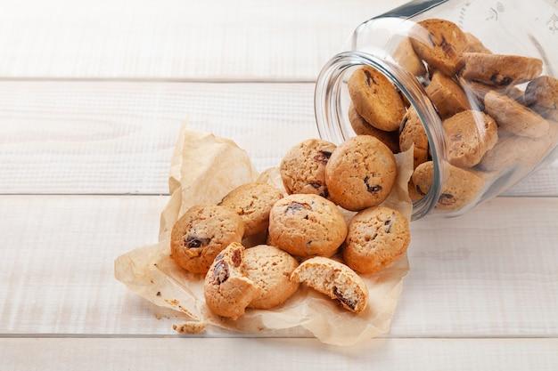 Biscoitos redondos doces com amoras, espalhados em banco de vidro transparente