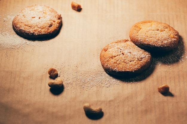 Biscoitos redondos em papel manteiga, com nozes e farinha