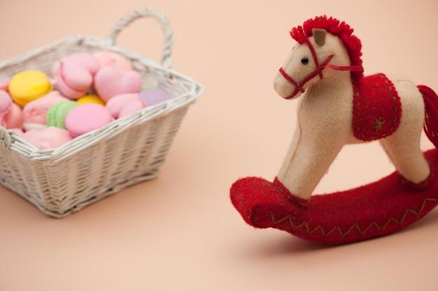 Biscoitos rosa e biscoitos redondos coloridos em uma cesta de vime e cavalo de brinquedo no dia dos namorados