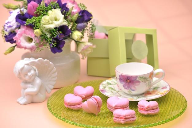 Biscoitos rosa em forma de coração em um prato com anjos e flores no dia dos namorados