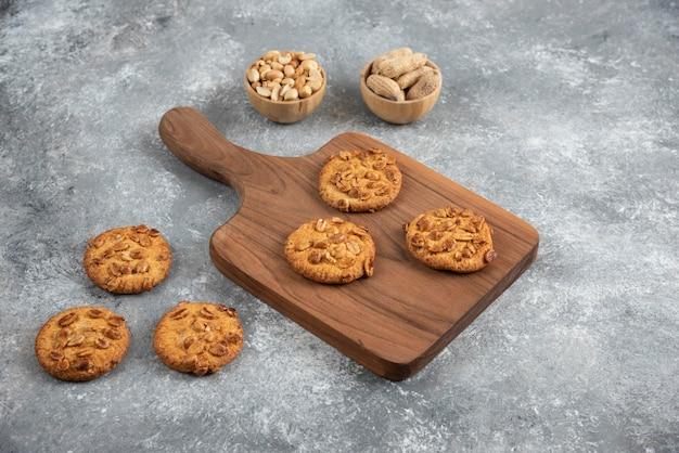 Biscoitos saborosos com amendoim orgânico e mel na placa de madeira.
