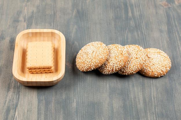 Biscoitos saborosos com pãezinhos em uma mesa de madeira