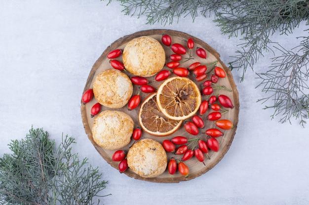 Biscoitos saborosos com rodelas de laranja e frutos de rosa.