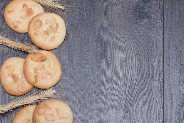 Biscoitos saborosos das cookies com amêndoa e trigo no fundo de madeira.