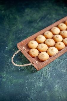 Biscoitos saborosos de vista frontal dentro de uma caixa de madeira em uma superfície azul escura