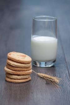 Biscoitos saborosos dos bolinhos com amêndoa e trigo na placa. um copo de leite ou iogurte com
