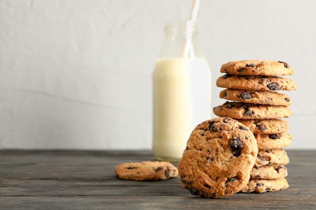 Biscoitos saborosos dos pedaços de chocolate e garrafa de leite na mesa de madeira. espaço para texto