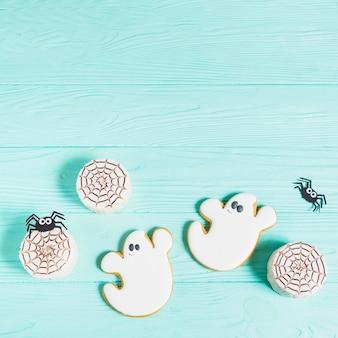 Biscoitos saborosos perto de aranhas de decoração e pão de gengibre
