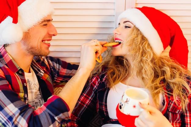 Biscoitos saborosos uma xícara e um casal feliz com chapéus de palhaço sultana