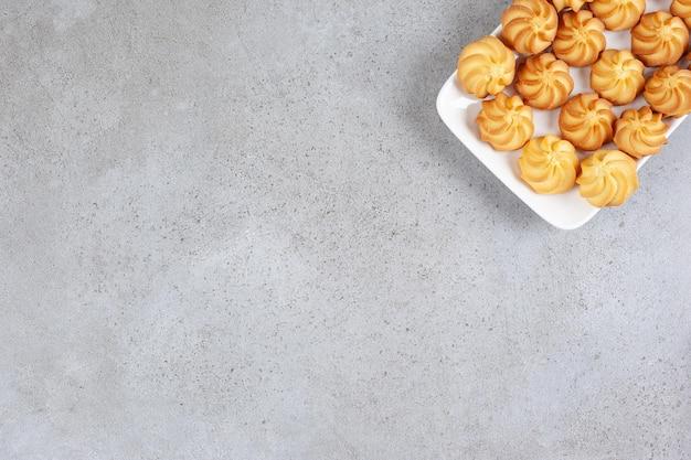 Biscoitos salgados dispostos em um prato branco sobre fundo de mármore.
